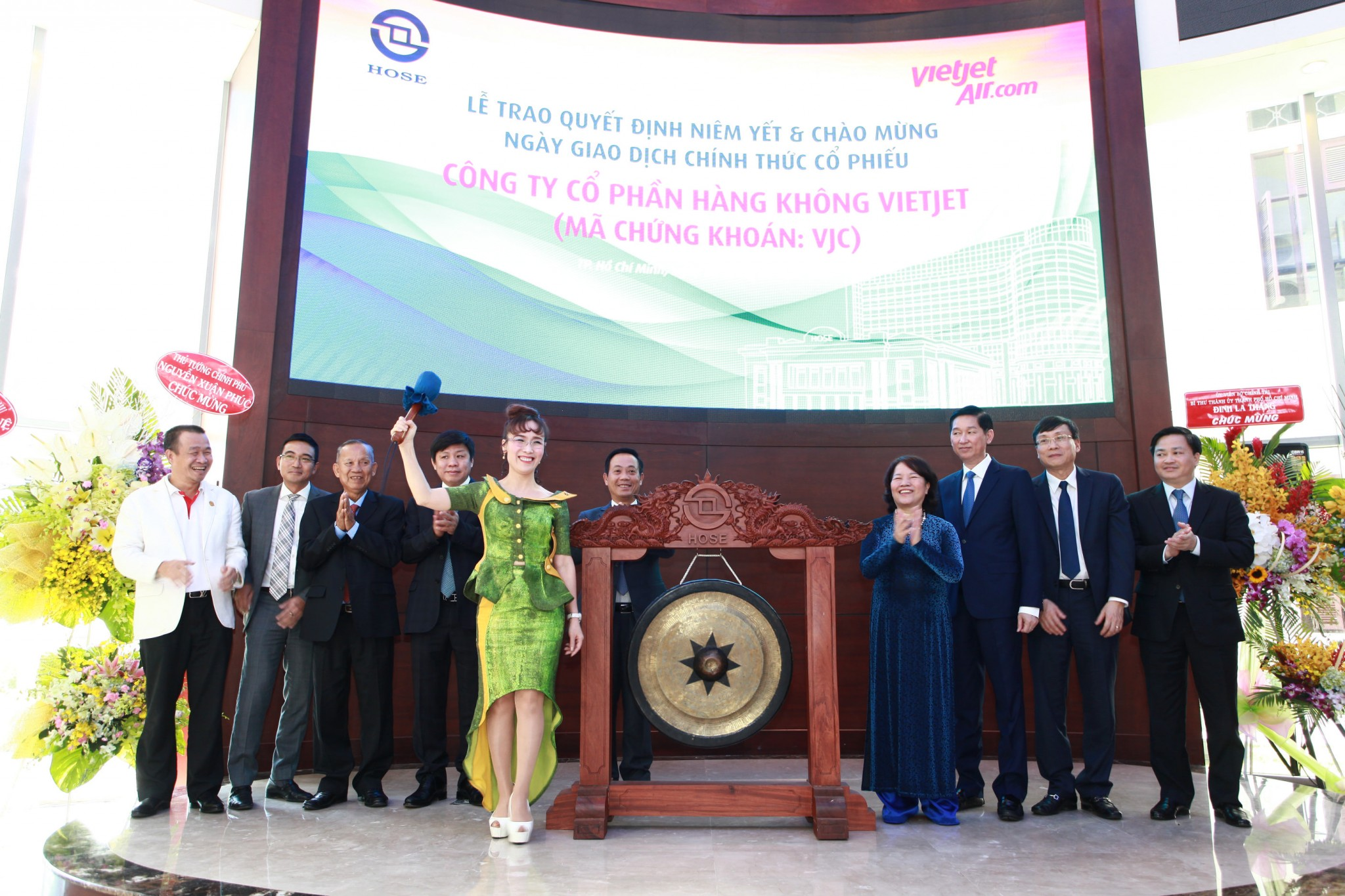 "Nguyen Thị Phương Thao (5th from left) ""hits"" the gong for the first time, marking the airline's listing on HOSE"